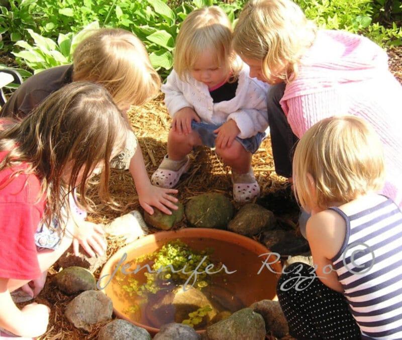 Kids in a backayrd tadpole habitat for summer learning
