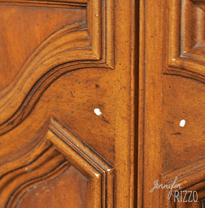 Old cabinet holes puttied for new knob placement in a cabinet makeover