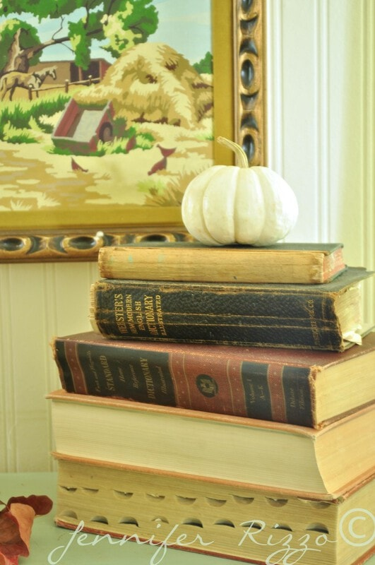 Grocery store pumpkin on book stack