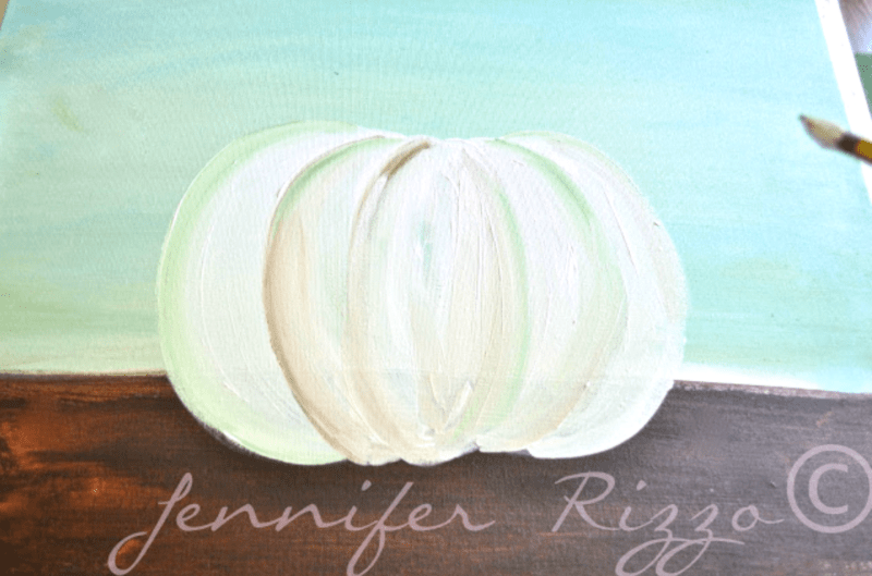 Painting a pumpkin on a canvas