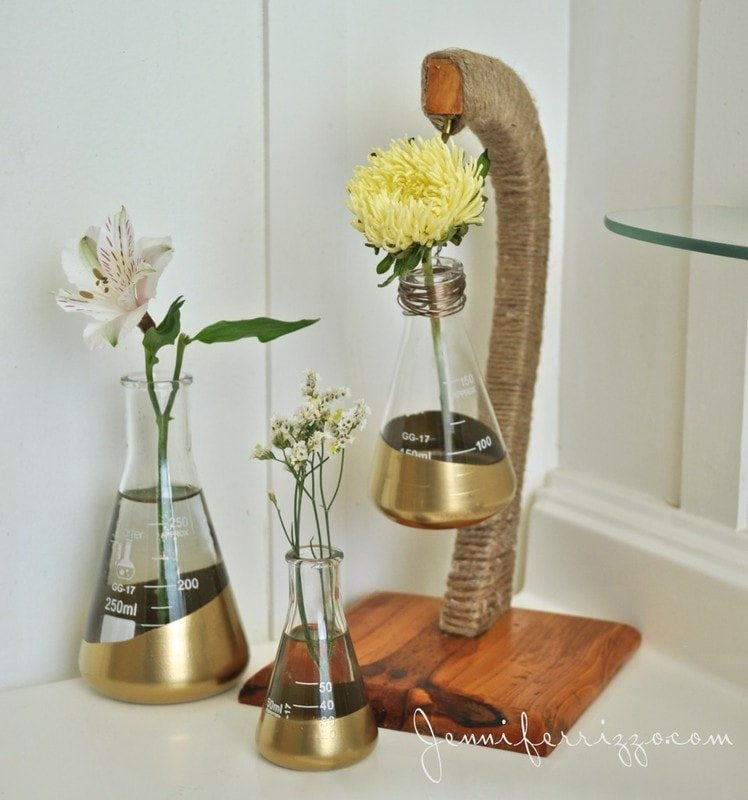 Labratory-beakers-dipped-in-gold-paint-and-a-recycled-banana-hook-make-a-fun-display-for-flowers