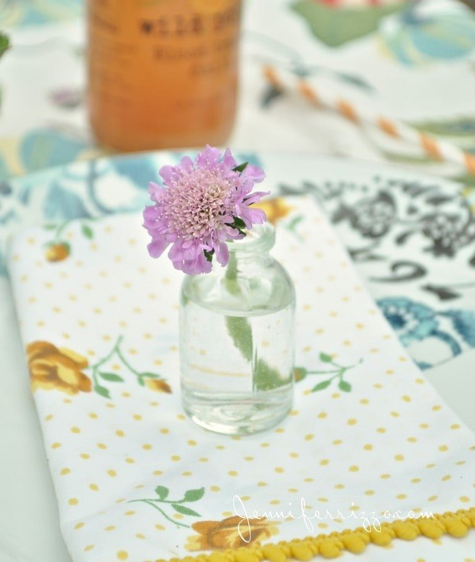 Pin cushion flowers in mini-glass bottles