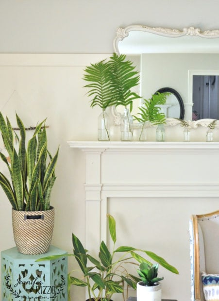 Faux mantel with ferns and vintage glass bottles
