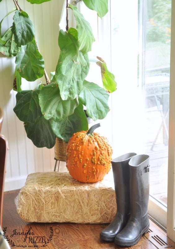 easy decor boots and pumpkin on straw bale