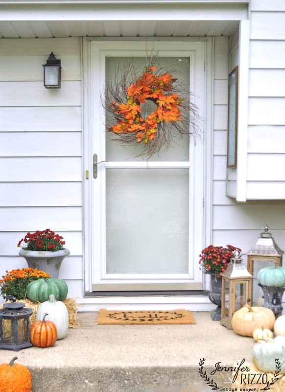 Fall wreath on front door and mums and pumpkins as decor