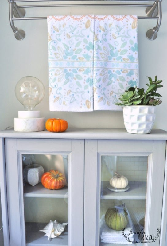 Bathroom cabinet decorated for fall and Jennifer Rizzo hand towels