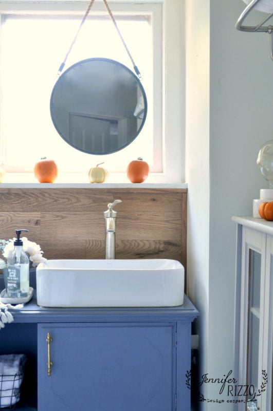 pedestal sink and wood wall with pumpkins as fall decor