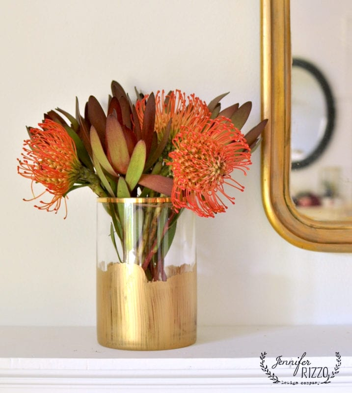 Protea and purple and green foliage in a gold paint stripe vase