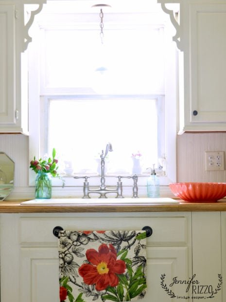 Earyl spring kitchen windowsill decorating idea. Great idea use a towel bar uner that fake cabinet drawer under the sink to hold dish towels.