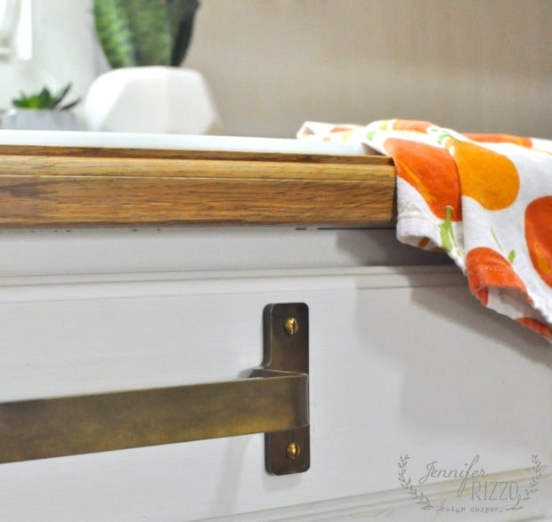 Brass towel bar under sink to hang dish towels on to dry.