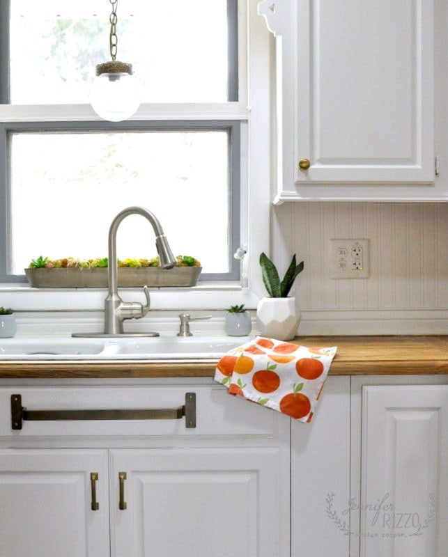 KItchen sink with brass towel bar mounted underneath. What a great way to keep your dish towels dry!