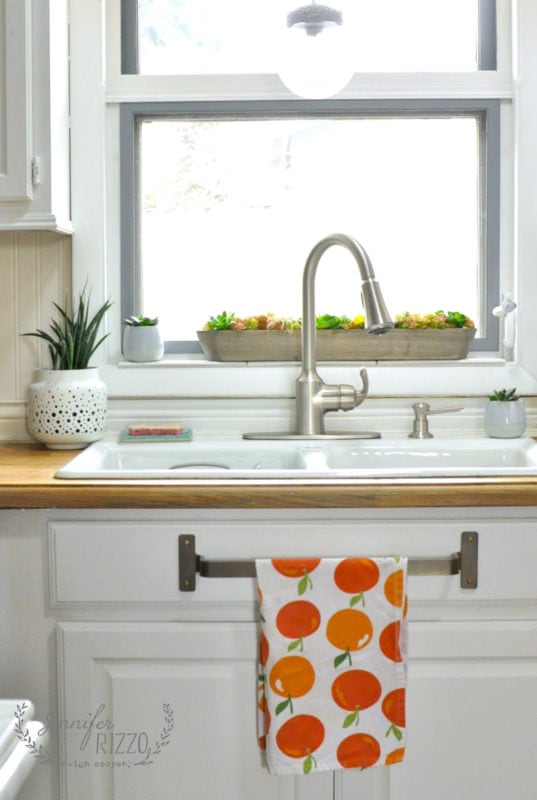 Kitchen sink with gray painted window and brass towel bar under sink. What a great use of the fake drawer under the sink.