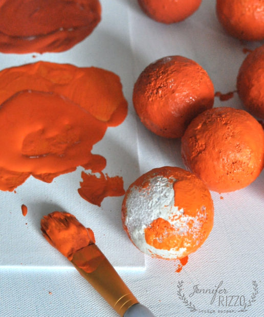 Paint a dark orange paint onto faux oranges
