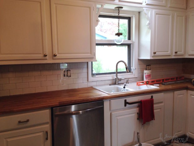 Kitchen with white subway tile installation in progress