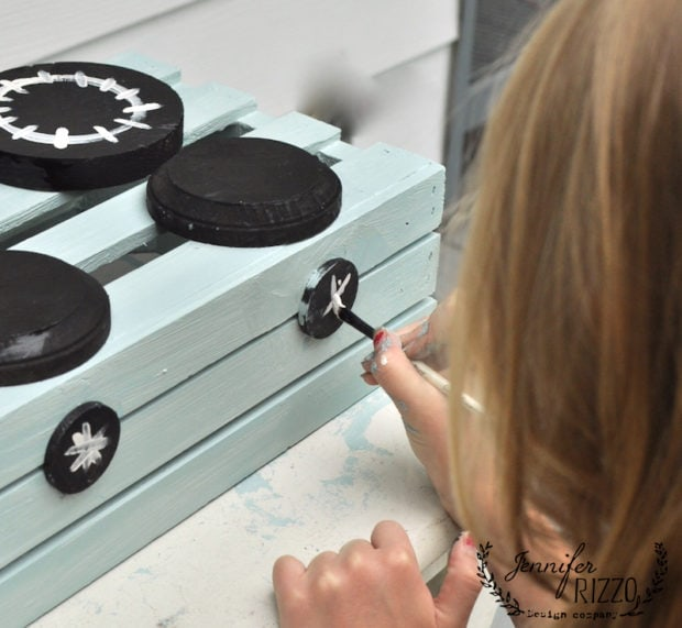 Painting design on play stove knobs
