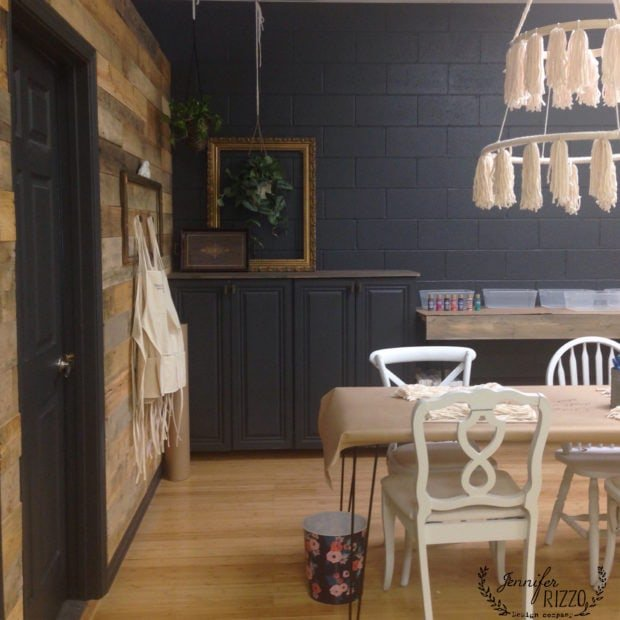 Makery space in The Collective lhe in Lisle< IL with dark gray wall paint, mismatched chairs and wood wall.
