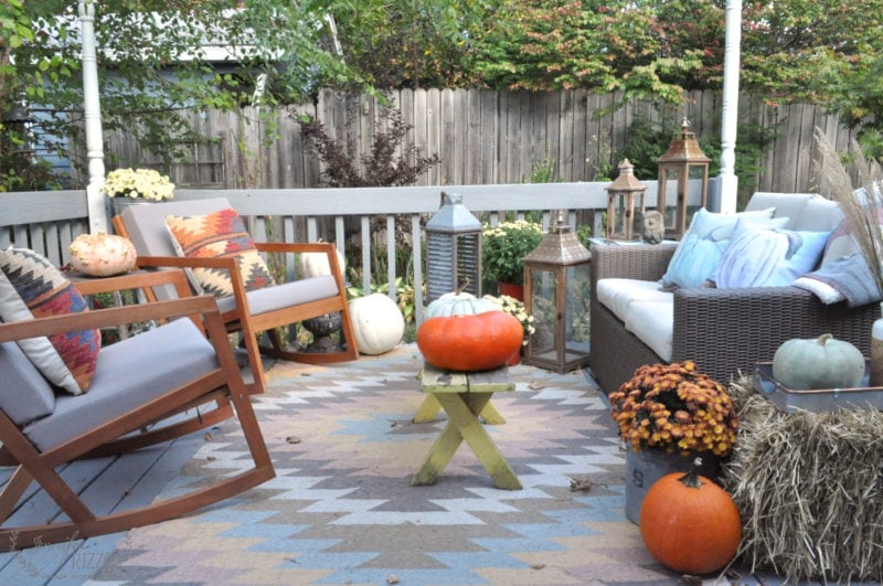 BAck deck decorated for fall with pumpkins and mum, with a Killim rug and pillows