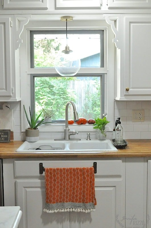 Kitchen window view with orange towel wood countertops