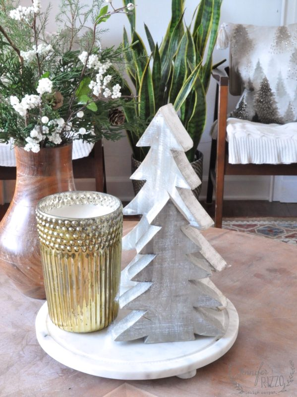 Wood trees and gold candle on cofeee table