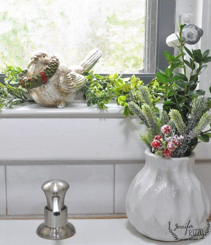 Kitchen window with a bird and faux greenery Jennifer Rizzo Christmas ktichen
