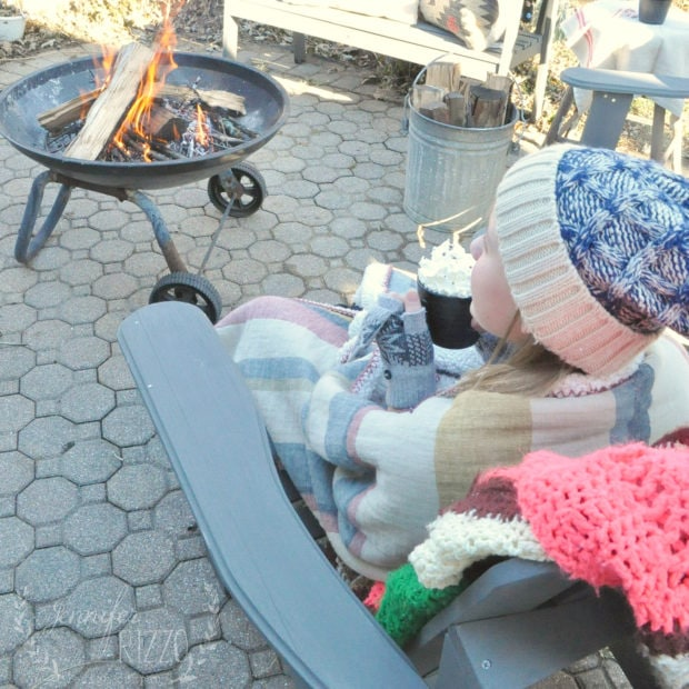 Enjoying hot cocoa in a blanket for an outdoor winter party