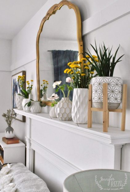 Faux fireplace mantel with white vases and yellow flowers. And spring home decorating refresh with flowers