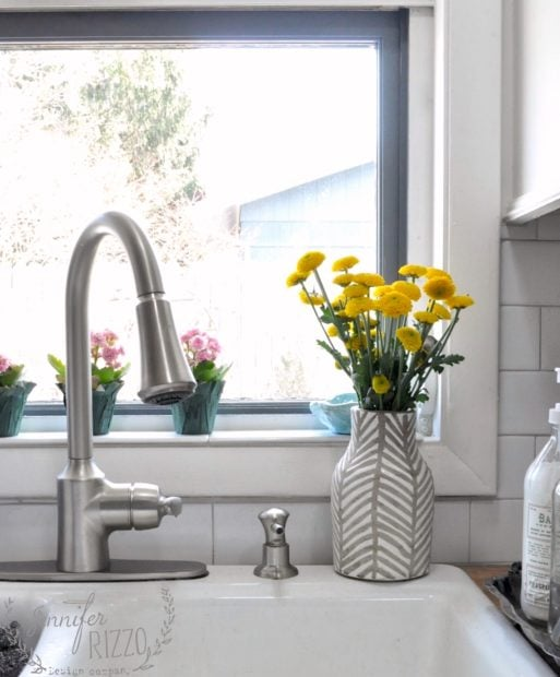 Kitchen sink with yellow flowers on sill