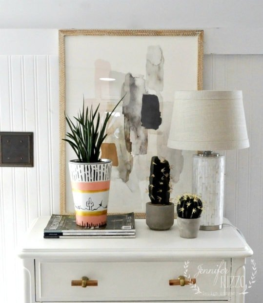 Fun,modern vignette with cactus, art from Minted, and a boho pink and gold vase.