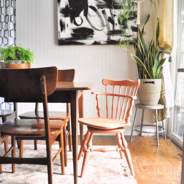 Boho dining room with abstract art and painted dining room chairs