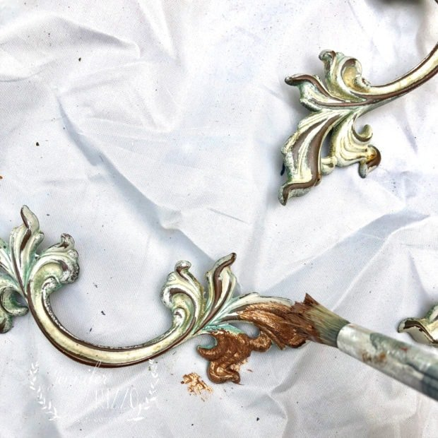 Painting old drawer handles with copper paint as an inexpensive way to update them.
