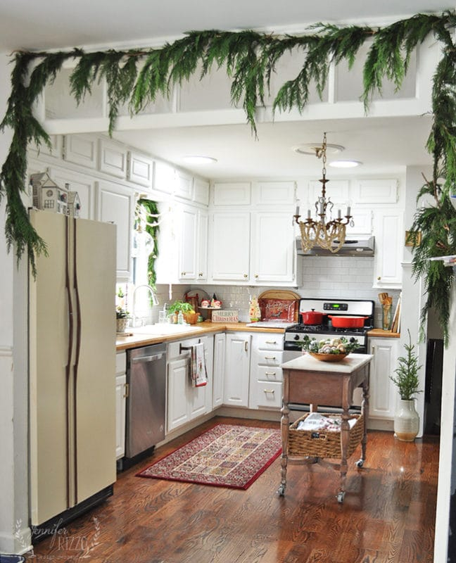 Jennifer Rizzo's white kitchen decorated for the holidays with vintage table as island