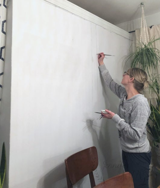 Jennifer Rizzo painting birch tree mural on wall