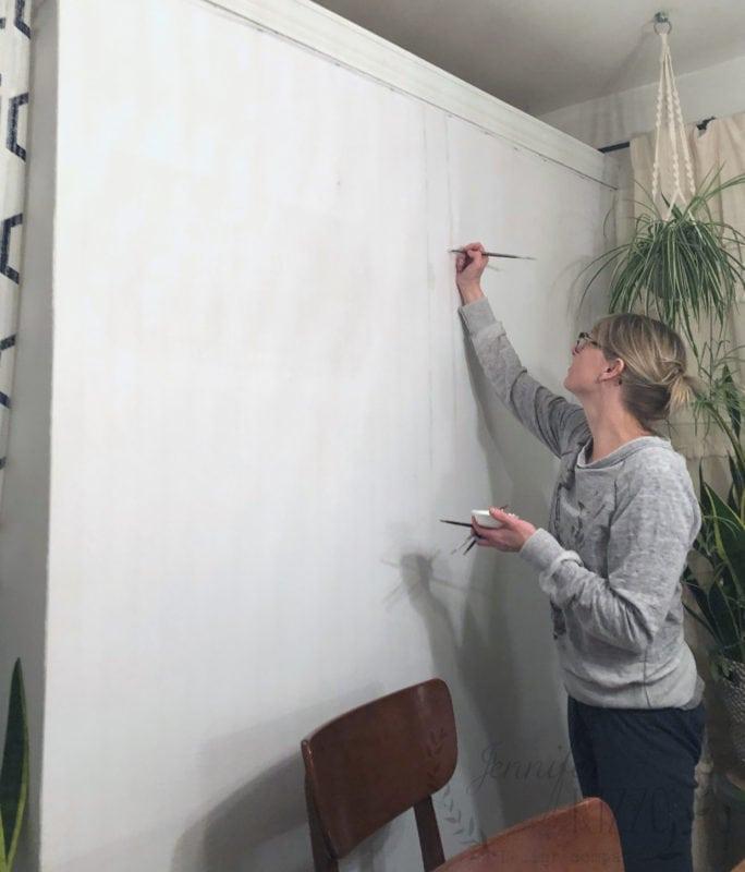 Jennifer Rizzo painting birch tree mural on wall