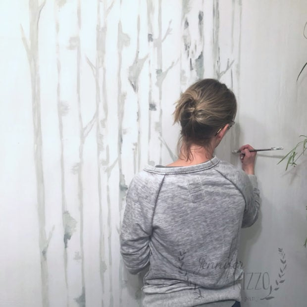 Jennifer Rizzo painting birch tree wallpaper on wall as a mural
