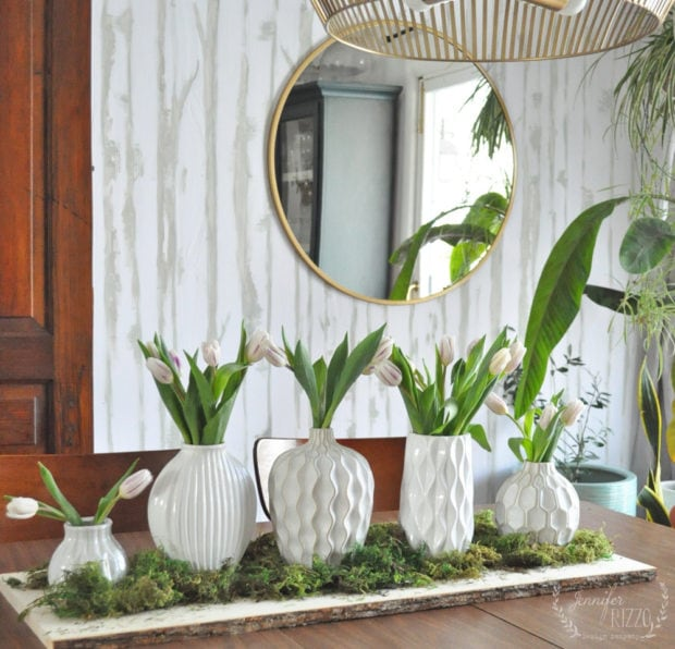 Easy spring centerpiece on a wood slab with vases and moss Jennifer Rizzo