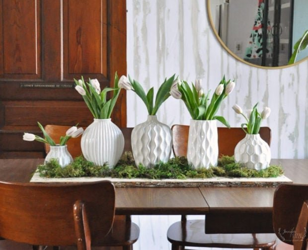 Wood slab and moss with five white vases as a spring centerpiece Jennifer Rizzo