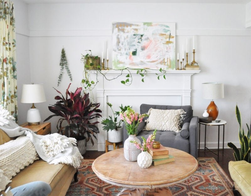 Boho living room with plants on mantel and abstract art Jennifer Rizzo