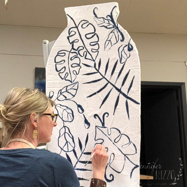 Jennifer Rizzo painting modern pattern on a giant chinoiserie cardboarad vase on a DIY cardboard vase for a window display