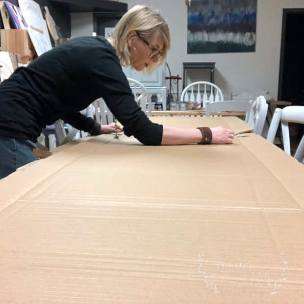 Jennifer Rizzo sketching out cardboard shapes for giant display vases