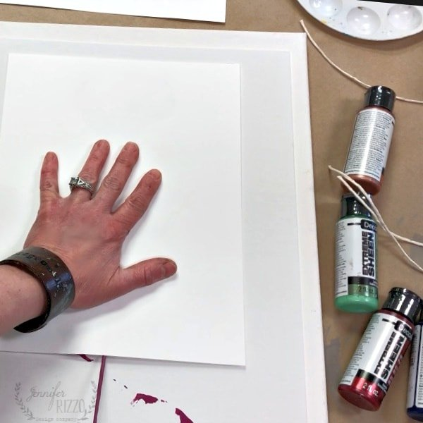 Place hand lightly on paper to hold it in place and pull string