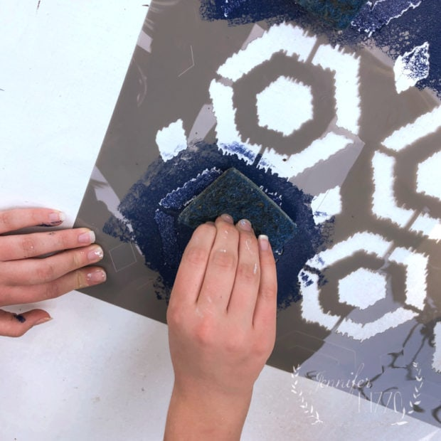 Using a kitchen sponge to stencil a large stencil on a deck