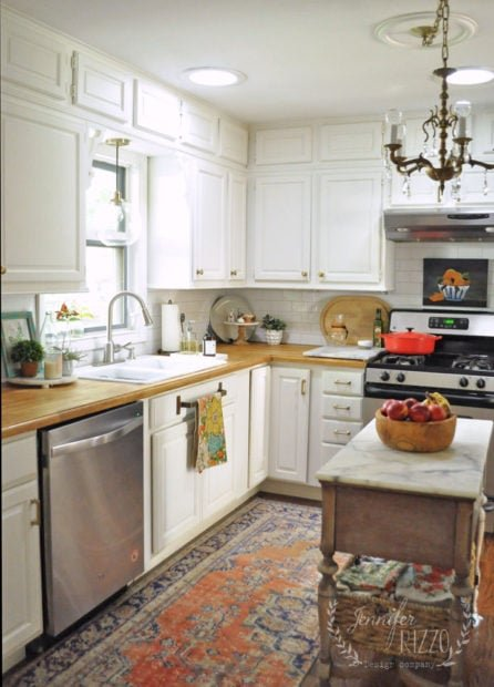 White kitchen with vintage woven rug and wood counter tops