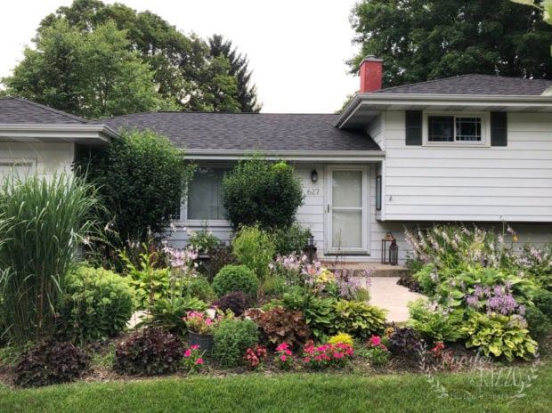 Landscaping in front of a white split level house with gray shutters