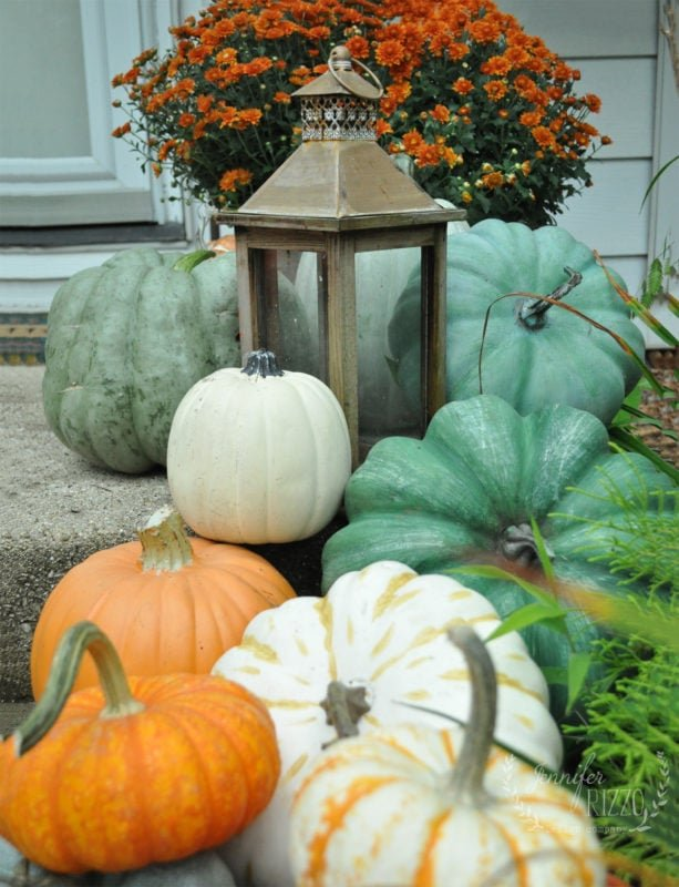 Faux and real pumpkins mixed on front porch