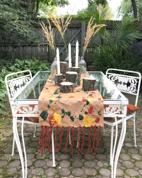 Outdoor fall setting with branches, grass and a DIY kraft apper table runner