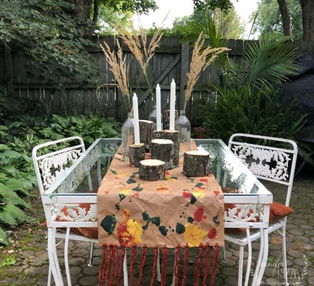 Fall table setting with grasses, tree branches, and paper.
