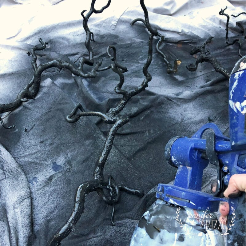 Spray painting branches black for spooky decor