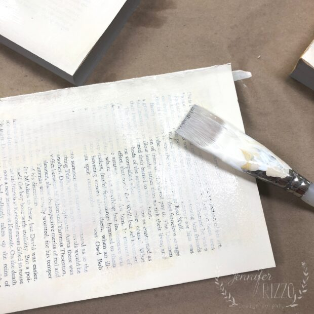 Paint and old book with white craft paint to upcycl e and repurpose books