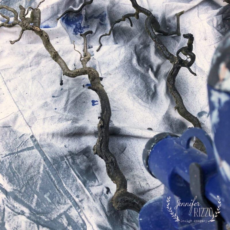 Spray painting branches black for holiday decor