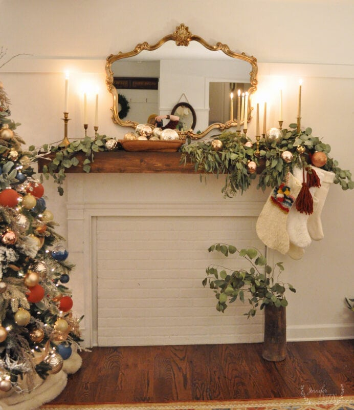 FIreplace mantel decorating idea with eucalyptus, brass candle sticks and mercury glass ornaments